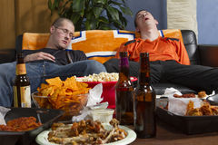 Two tired men after watching sports game on TV, horizontal Stock Images