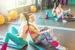 Two tired sports girls resting after active workout. Sitting on the platform, leaned on backs. Sport life theme photos royalty free stock image