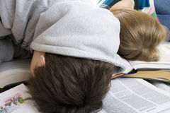 Two tired students sleep on books Stock Images