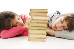 Two tired teenage girls with pile book Royalty Free Stock Photography