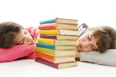 Two tired teenage girls with pile colored book Royalty Free Stock Images