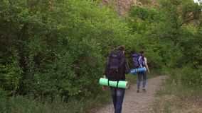Two tired travelers walk in the mountains. Slow mo. Two tired travelers walk in the mountains along a narrow trail with large backpacks behind them. Back view stock video