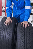 Two tires with mechanic in workshop Stock Photo