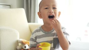 Child eating cereal puffs stock video footage