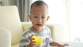 Child eating cereal puffs stock footage