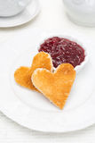 Two toast bread in the shape of hearts and berry jam in a bowl Stock Photo