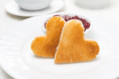 Two toast bread in the shape of hearts and berry jam Royalty Free Stock Image