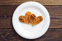 Two toast bread in the shape of hearts stock image