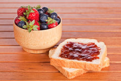Two toast with jam, blueberries and strawberries Royalty Free Stock Image