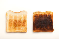 Two toasted slices of bread, perfect and burnt Royalty Free Stock Photography