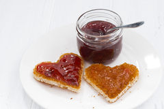 Two toasts in heart shape with fruit jams on plate Stock Images