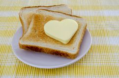 Slices of toast bread and butter. Two toasts with heart shaped butter on a yellow tablecloth Stock Photo