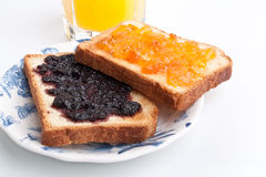 Two Toasts with Jam. Two Toasts Spread with Jam and a Glass of Orange Juice Stock Images