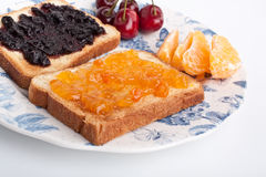 Two toasts with jam. Two toasts with orange and cherry jam Royalty Free Stock Photo