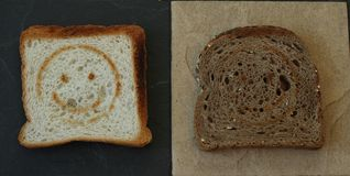 Two toasts. One smiling white bread toast and one grey bread toast Stock Photo