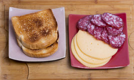 Two toasts and salami with cheese on red and gray plates Stock Photo
