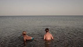 Two toddler boys enjoying summer holidays in the sea stock footage