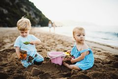 Two toddler children playing on sand beach on summer holiday. Two toddler children playing on sand beach on summer family holiday royalty free stock photo