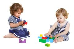 Two toddler girls playing with building blocks Royalty Free Stock Images
