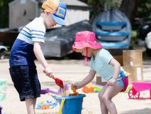 Two Toddlers, a Boy & a Girl, Dressed with Good Sun Protection, Play on a Sandy Beach Building Sand Castles royalty free stock photography