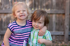 Two Toddlers, Hugging and Smiling. Two Caucasian toddlers, blonde and red-haired, hugging, grinning royalty free stock images