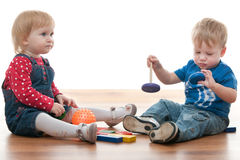 Two toddlers are playing with blocks. Two toddlers are playing with toys sitting on the floor; isolated on the white background stock photography