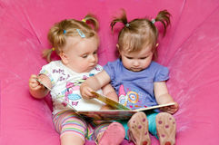 Two toddlers reading together. Two toddler girls sitting together in pink chair, reading a storybook together Royalty Free Stock Photography