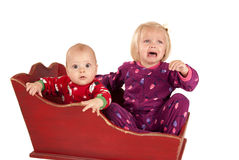 Two toddlers in sleigh one is sad and crying Stock Images