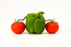 Two tomato and one green capsicum. Two red tomato and one green bell pepper, isolated on white Stock Photo