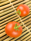 Two Tomatoes on Bamboo Stock Images