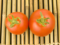 Two Tomatoes on Bamboo Royalty Free Stock Image