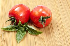 Two tomatoes and basil Royalty Free Stock Photography