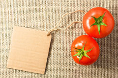 Two tomatoes with cardboard tag on sacking Royalty Free Stock Image