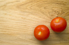 Two Tomatoes on Chopping Board. Flat lay shot of two tomatoes Royalty Free Stock Photos