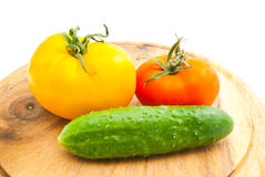 Two tomatoes and cucumber on cutting board Royalty Free Stock Images
