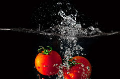 Two tomatoes falling into water Royalty Free Stock Photos