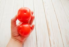 Two tomatoes in a female hand over white wooden background.  Royalty Free Stock Photos
