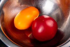 Two tomatoes in a iron salad bowl royalty free stock photos