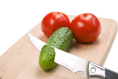 Two tomatoes and one chopped cucumber on cutting b Stock Images