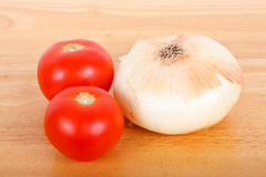 Two Tomatoes and an Onion on a Wood Board Royalty Free Stock Image