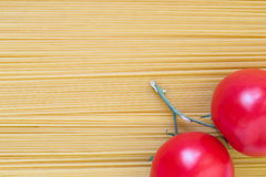 Two tomatoes on spaghetti background. Pasta spread out as a background in the corner of red tomato Royalty Free Stock Photo