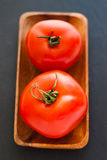 Two tomatoes in tray Stock Photography