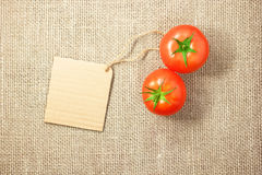 Two tomatoes vegetable and price tag on sacking background textu Stock Photos