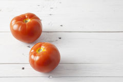 Two tomatoes on a white table Royalty Free Stock Photos