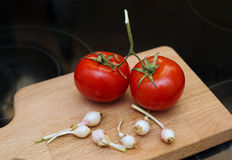 Two tomatoes and young garlic on wooden cutting board. In the kitchen Royalty Free Stock Photo