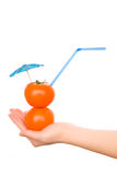Two tomatos with straw and cocktail umbrella Royalty Free Stock Image