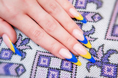 Two tone manicure with blue and yellow varnish. In the ukraine tradition Royalty Free Stock Images