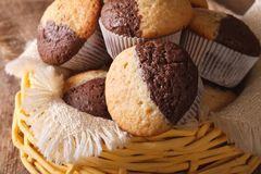 Two-tone muffins orange and chocolate closeup in basket Stock Image