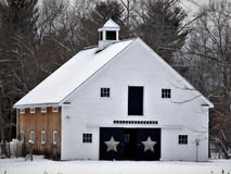 White New England barn in snow covered field. White cupola,; 6 pane windows,.l brown wood siding, stars on doors, four-story stock image