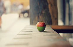 Two-toned apple sits on an outdoor bar Royalty Free Stock Images